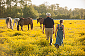 Caucasian man and granddaughter in field with horses