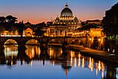St. Peter's Basilica and Tiber River illuminated at dusk, Rome, Lazio, Italy