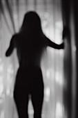Silhouette of Nude Woman Standing Near Window, Rear View