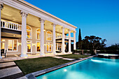 Mansion with Columns and Swimming Pool at Dusk