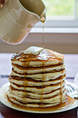 Maple Syrup Being Poured Over Stack of Pancakes