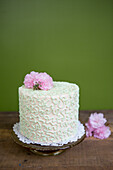 Layered Cake with Pink and White Icing and Pink Flowers