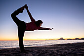Woman in Yoga Pose on Beach at Sunrise