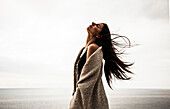 Young Woman Portrait with Head Back and Long Hair Blowing in Wind with Ocean in Background