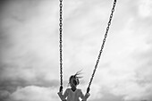 Girl on Swing Against Gray Sky, Rear View