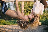 Young Boy and Girl Hanging Upside Down Kissing