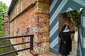 Benedictine nun at gate, Abbey at Burg Dinklage, Lower Saxony, Germany