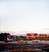 PESCADERO, BAJA CALIFORNIA SUR, MEXICO. A young woman sits in a lounge bed on an empty beach enjoying the sunset with a resort in the background.