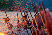 Salmon skewered on redwood stakes cooks on open fire along the Klamath River.