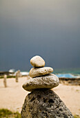 JAMAICA. Stacks of rocks are placed on a beach for good luck under a threatening sky.