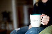 A mug wanting a smile sits on a woman's lap.