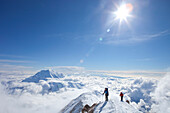 Two male climbers at the ridge between 14k and 17k camp on Mount McKinley, Alaska. They are above the clouds in blue sky and the sun is shining. Nevertheless it is very cold.    Mount McKinley, native name Denali, is the highest mountain peak in North Ame