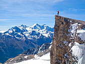 A male mountaineer is standing on the summit of the Barrhorn, a mountain peak of 3610 meter in the Swiss Alps. It is one of the highest summits in Europe to be accessible to experienced hikers. The region of Wallis is home to over 40 mountain peaks higher