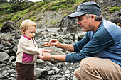 Father puts sea star in toddler girl's hand near rocky tidepools at Patrick's Point State Park, California.