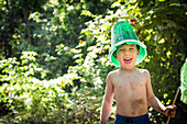 Toddler boy jokes with a bucket on his head and butterfly net in hand while next to creek in Bidwell Park, Chico, California.
