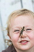 Toddler girl smiles at camera with Sagebrush lizard on nose in Chico, California.