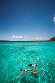 A couple float on their backs in clear teal Caribbean water.