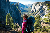 A female backpacker stops to take in the views of Yosemite National Park on a sunny day.