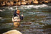 A fly fisherman pulling in a fish in Squamish, British Columbia.