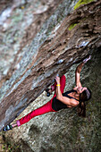 Strong Female bouldering on overhanging rock in Idaho