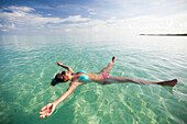 A young woman floats on her back with her limbs stretched out in shallow turquoise water while on vacation in Cayo Coco, Cuba.
