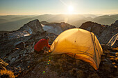 A hiker sets up a tent on the summit of Saxifrage Peak, Pemberton, BC, Canada.