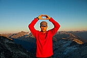 A hiker raises his hands to circle the full moon while camping on Saxifrage Peak, Pemberton, BC, Canada.