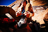 A woman ties her rock climing shoes as she gets ready for her next climb. Indian Creek, Utah
