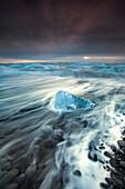 Glacial ice from Breiðamerkurjökull sits on the beach  of the coast at Breiðamerkursandur, Iceland, also known as the Jokulsarlon.