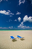 Two empty beach chairs sit in ankle deep water facing the turquoise ocean in Cayo Coco, Cuba.