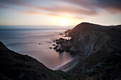 A landscape view of the rocky shore and sunset from the Chimney Rock Trail in the Point Reyes National Seashore of California.