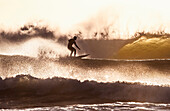 surfer in heavy surf at dusk