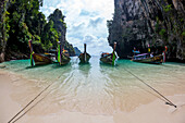Six wooden long tail boats anchored to a small sandy beach on a island in Krabi, Thailand.