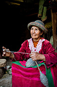 An older woman spins wool in Ayacucho, Peru, wearing traditional clothes.