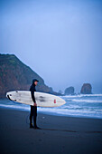 Paul Burgin prepares to paddle out for a cold winter surf session at Rockaway beach south of San Francisco California
