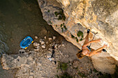 A women in shorts and a blue top rock climbing on a steep route above water in Rodeallr Spain. There is blue a raft at the base of the rock wall where the climber's had rafted in to access the cliff.