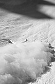 A male skier expertly avoids his sluff at the bottom of a run on a face called Abandonment, Haines, Alaska