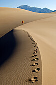 A woman walks the ridge of a dune in the vast Great Sand Dunes National Park, Colorado.  The park hosts the tallest sand dunes in North America, rising 750 feet above the floor of the San Luis Valley.