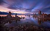 A long exposure at twilight shows the motion of clouds passing over the otherworldly Tufa stacks along the shore of California's famous Mono Lake.  The soft glow of twilight and symmetry of the composition draw the eye through the scene.