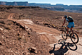A woman in her early thirties mountain bikes the White Rim Trail near Moab, Utah.