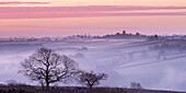 Mist shrouded countryside looking towards the village of Morchard Bishop in winter, Devon, England, United Kingdom, Europe
