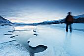 Ein Mann läuft auf einem zugefrorenen See im Abisko National Park, Schweden, Skandinavien, Europa