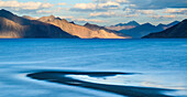The turquoise, saline water of Tso Pangong, backed by mountains in the evening sun, Ladakh, India, Asia