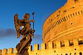 Angel statue on Ponte Sant' Angelo bridge at dusk with Castel Sant' Angelo, Rome, Lazio, Italy, Europe