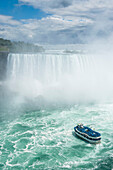 Tourist boat in the mist of the Horseshoe Falls, or Canadian Falls, Niagara Falls, Ontario, Canada