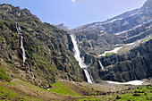 Waterfalls cascade down the karst limestone cliffs of the Cirque de Gavarnie, Pyrenees National Park, Hautes-Pyrenees, France, Europe