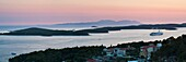 Pakleni Islands (Paklinski Islands) and Vis Island, a Mediterranean cruise ship moored at sunset, seen from Hvar Island, Dalmatian Coast, Adriatic Sea, Croatia, Europe