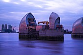 Section of the River Thames Flood Barrier at dusk with Canary Wharf and O2 Arena in the background, London, England, United Kingdom, Europe