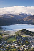 Aerial view over Keswick to a mist covered Derwent Water, Lake District National Park, Cumbria, England, United Kingdom, Europe