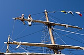 Detail of main mast of tall ship with two seamen on top yard securing sail, Whitehaven, Cumbria, England, United Kingdom, Europe